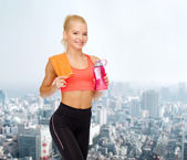 Smiling sporty woman with water bottle and towel — Stockfoto