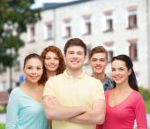 Group of smiling teenagers over campus background — Stock Photo