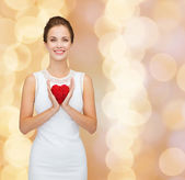 Smiling woman in white dress with red heart — 图库照片
