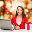 Smiling woman with credit card and laptop — Stock Photo #53410701