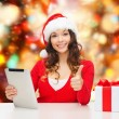 Smiling woman in santa hat with gift and tablet pc — Stock Photo #53411073