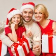 Smiling family holding gift boxes and sparkles — Stock Photo #53413043