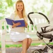 Happy mother with book and stroller in park — Stock Photo #53413783