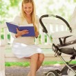 Happy mother with book and stroller in park — Stock Photo #53413789
