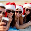 Group of friends in santa hats with smartphone — Stock Photo #53414161