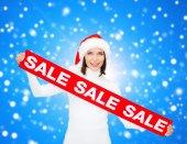 Usmívající se žena v pomocníka čepice santa s nápis-na prodej — Stock fotografie