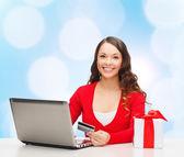 Mujer sonriente con tarjeta de crédito y portátil — Foto de Stock