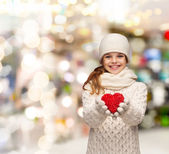 Dreaming girl in winter clothes with red heart — Stock Photo