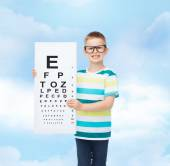 Smiling boy in eyeglasses with white blank board — Stock Photo