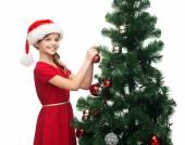 Smiling girl in santa helper hat decorating a tree — Stock Photo