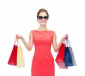 Smiling woman in red dress with shopping bags — ストック写真