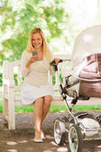 Happy mother with smartphone and stroller in park — Stock Photo