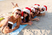 Group of friends in santa hats with smartphone — Stock Photo