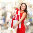 Smiling woman in red dress with gift boxes — Stock Photo #53452503