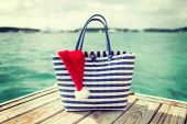 Close up of beach bag and santa helper hat — Stock Photo