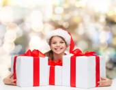 Smiling girl in santa helper hat with gift boxes — Stock Photo