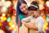 Chica feliz de la madre y el niño con caja de regalo — Foto de Stock