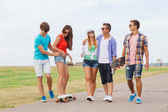 Group of smiling teenagers with skateboards — Stock Photo