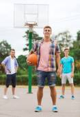 Group of smiling teenagers playing basketball — Stock Photo