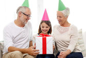 Smiling family in party hats with gift box at home — Stock Photo