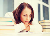 Bored young woman with many books indoors — Stock Photo