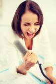 Woman shouting into phone in office — Stock Photo