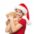 Smiling girl in santa helper hat with teddy bear — Stock Photo #53672787