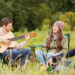 Group of smiling friends with guitar outdoors — Stock Photo #53675425