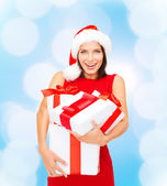 Smiling woman in red dress with gift boxes — Стоковое фото