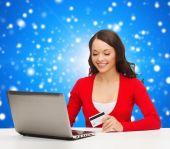 Femme souriante avec carte de crédit et d'ordinateur portable — Photo