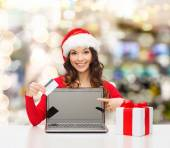 Smiling woman with credit card and laptop — Stock Photo