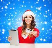 Femme en bonnet de noel avec les tablet pc et carte de crédit — Photo