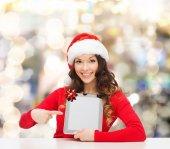 Lachende vrouw in kerstmuts met een geschenk en tablet pc — Stockfoto