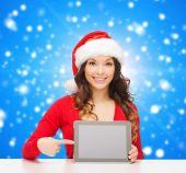 Femme souriante en bonnet de noel avec cadeau et tablet pc — Photo
