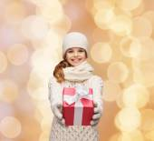 Dreaming girl in winter clothes with gift box — Stock Photo