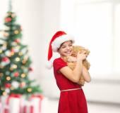Smiling girl in santa helper hat with teddy bear — Stock Photo