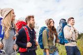 Grupo de amigos sorridentes com mochilas para caminhadas — Fotografia Stock