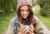 Uśmiechnięta młoda kobieta z filiżanki i plecak pieszych — Zdjęcie stockowe