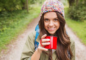 Smiling young woman with cup and backpack hiking — Stock Photo