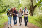 Group of friends with backpacks and tablet pc — Stock Photo