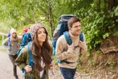 Group of smiling friends with backpacks hiking — Stockfoto