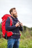 Man with backpack and binocular outdoors — Stok fotoğraf
