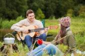 Smiling couple with guitar in camping — Stock Photo