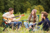 Group of smiling friends with guitar outdoors — Stock Photo