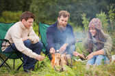Group of smiling friends sitting around bonfire — Stock Photo