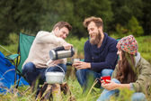 Group of smiling friends cooking food outdoors — Stock Photo