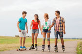 Group of smiling teenagers with roller-skates — Stock Photo