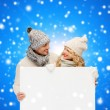 Smiling couple in winter clothes with white board — Stock Photo #53847903