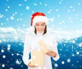 Femme souriante au chapeau d'assistance santa avec boîte-cadeau — Photo