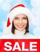 Femme souriante en bonnet d'assistance avec signe de vente — Photo